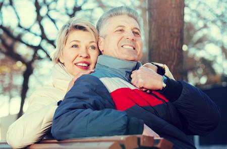 Mari senior positif et femme étreignant les uns les autres, assis sur un banc de parc Banque d'images - 77816858