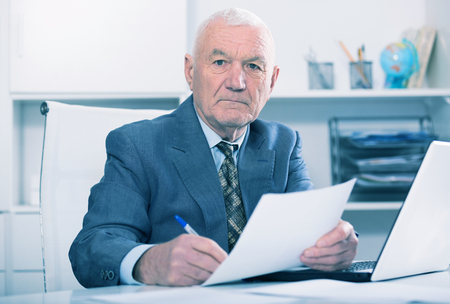Senior male worker working productively on project in office Stock Photo