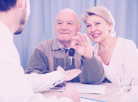 Old man and mature woman signing contract car lease and hand over keys to manager