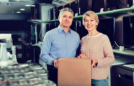 splurge: Mature couple are happy with choice and purchased consumer electronics for your home Stock Photo
