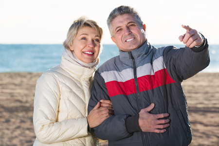 Cheerful married couple walk and husband points to wife to something interesting