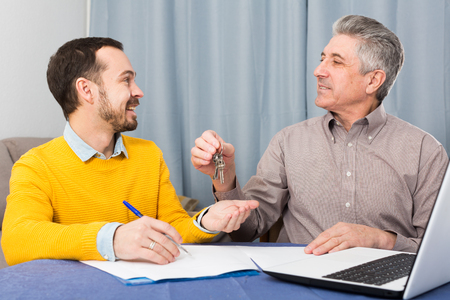 Mature man and young agent sign contract of rent apartments and hand over keys