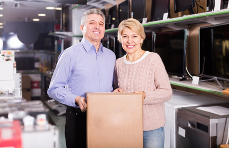 splurge: smiling mature married couple in shop packed household appliances into boxes for transportation to themselves home