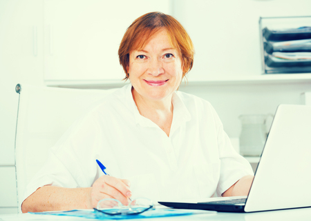 expertize: Smiling woman worker working effectively on project in office