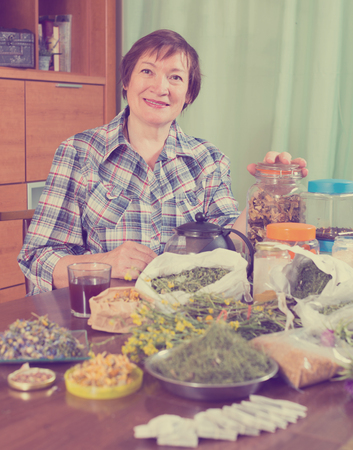 Smiling mature woman with medicinal herbs