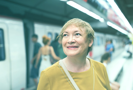 portrait of joyful  smiling elderly woman passenger in public train station in city Stock Photo
