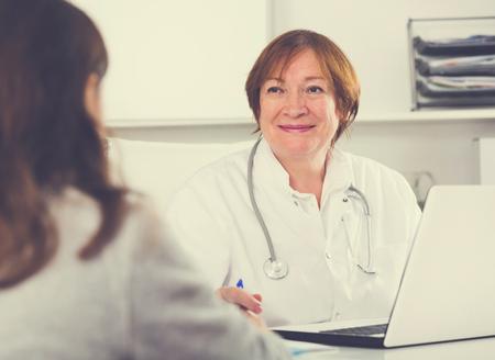 visitantes femeninas de consultoría sonriente mujer médico en el hospital
