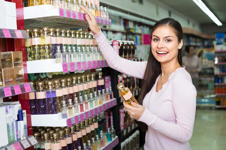 Happy young woman picking scented spray from shelf in cosmetics store