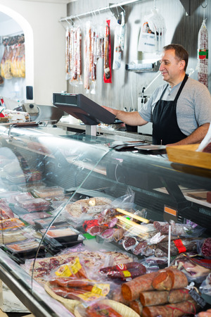 veal sausage: Experience senior salesman offering different sausages in delicatessen shop