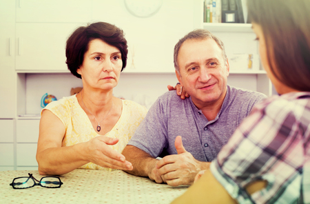 Serious retiree couple having conversation with adult daughter at home. Focus on man