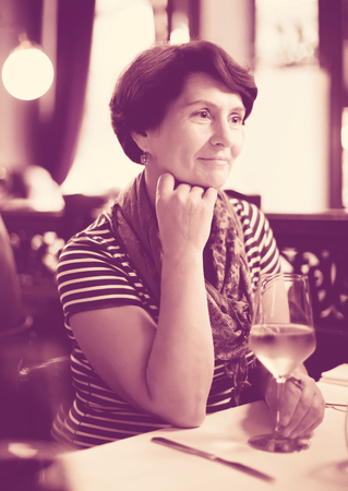 Woman sits at table at restaurant and holds glass with wine and smiling