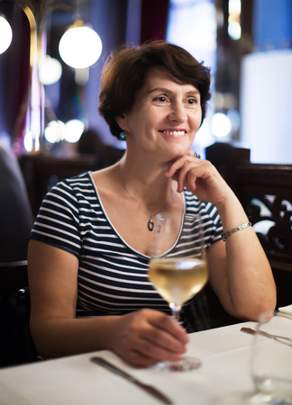 Elderly woman sits at table at restaurant and holds glass with wine and smiling