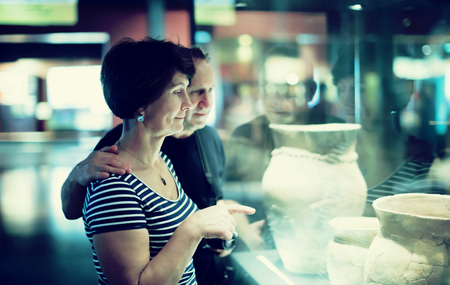 finds: Mature couple of tourists consider exhibit in museum Stock Photo