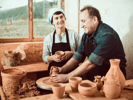 Smiling senior couple among the pottery at the workshop