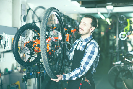 Smiling man master establishes a bicycle wheel in his workshop