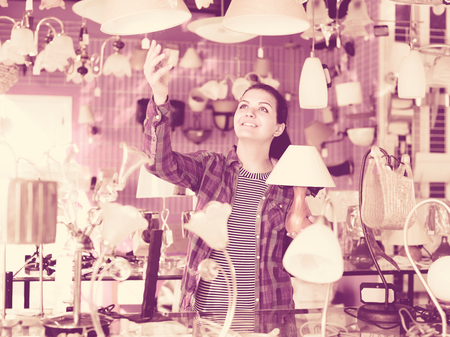 brightness: Smiling happy cheerful positive girl in lighter shop chooses stylish and modern chandelier lamp