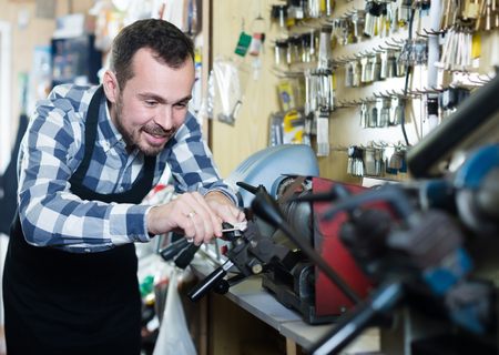 Young man worker working at forming key in repair workshop