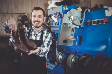 resulted: Cheerful male worker showing fixed shoes in shoe repair workshop