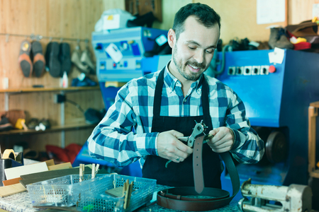 making hole: Young smiling glad friendly  male worker making hole in belt in specialized workshop Stock Photo