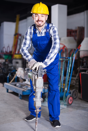 Smiling russian working man practicing his skills with pneumatic drill at workshop