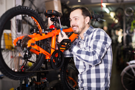 qualitatively: happy european man in sports workshop mounts bike using special tools