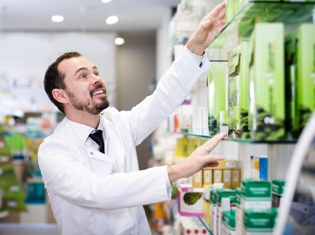 Young man pharmacist offering right drug in drugstore