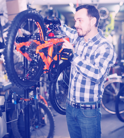 qualitatively: interested male mounts bicycle parts for assembly bike in sports shop