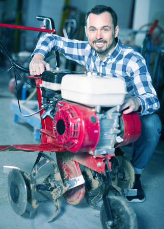Male 29-35 years old is starting to work with plough at workshop. Stock Photo