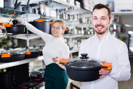 Male shop assistant recommends the casseroles for the kitchen in the crockery store Stock Photo