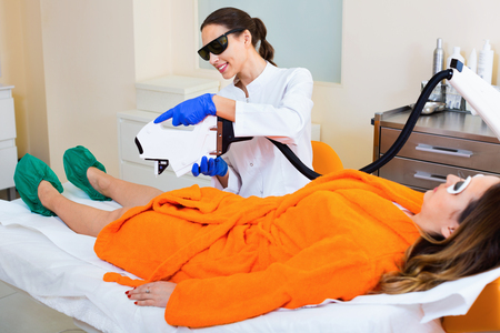 diligent: Young diligent friendly smiling female client doing laser hair removal from legs Stock Photo