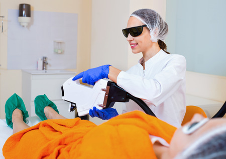 Young  friendly smiling female client doing laser hair removal from legs