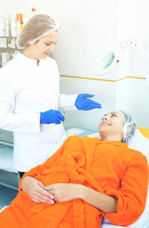 Positive woman doctor getting young client ready for beauty procedures