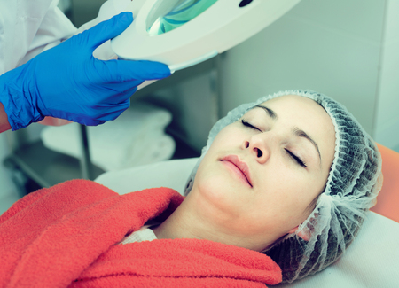Young woman doctor preparing to do beauty procedures to woman client
