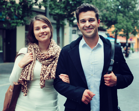 Beautiful young couple walking in city at autumn day Stock Photo