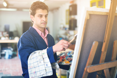 skilled: Creative male artist drawing picture with oil paints in studio