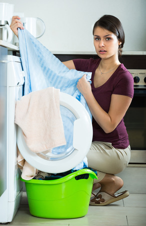 bed sheet: Unhappy young  brunette girl with dirty curtains near washing machine Stock Photo