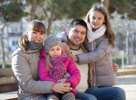 Cheerful family with smiling cute little daughters sitting on bench outside. Selective focus Stock Photo