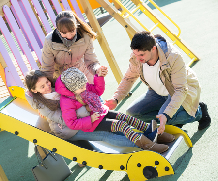 Happy young parents with two little daughters at sliding board outdoors. Selective focus
