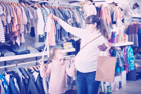 acquiring: Smiling mother and daughter show clothes for babies childrens clothing store