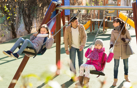 5s: Positive parents watching little daughters swinging at playground