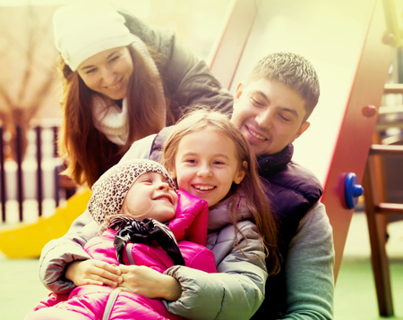 Portrait happy family with children resting fun on the playground Stock Photo