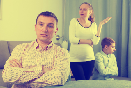 disagreeing: Pregnant mother and son having disagreement with father at home
