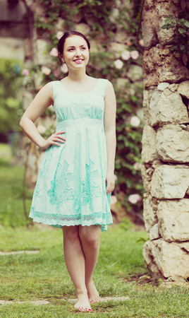 portrait of young smiling ethnicity woman in  dress  near roses in a garden Stock Photo