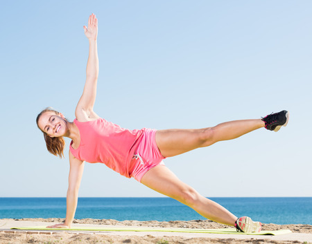 active young woman exercising on exercise mat outdoor at the seaside