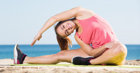 sportwoman: Happy young sportwoman doing gymnastics at sea beach on summer day Stock Photo