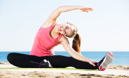 Young smiling woman doing yoga at beach on a sunny day