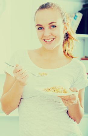 17 20: smiling girl with chestnut hair eating porrige