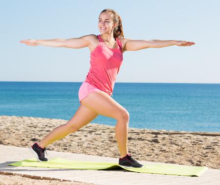 Happy active girl training  at sea beach