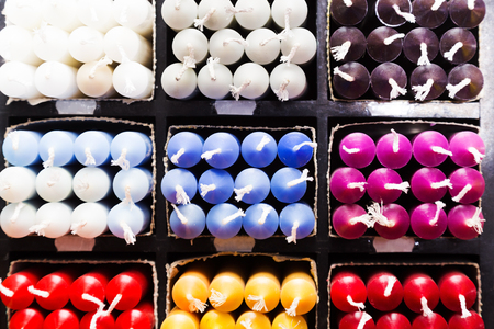 many multicolored paraffin candles lying on shelter in household shop Stock Photo
