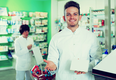 Positive man druggist in white coat giving advice to customers in pharmacy Stock Photo